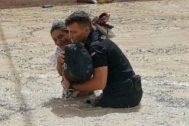 Un policía ayuda a una señora a salir de una zona inundada en Almoradí (Alicante).
