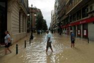 Varias personas cruzan una de las calles inundadas en Orihuela.