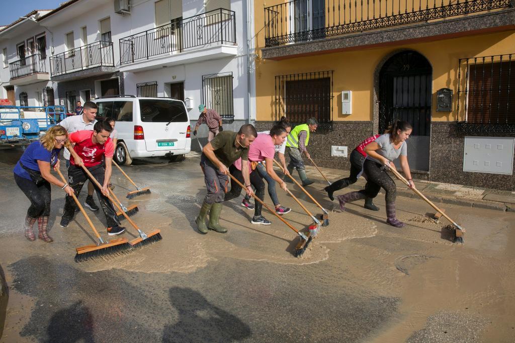 Vecinos de Villanueva del Trabuco, una de las zonas más afectadas por la gota fría en la provincia de Málaga, limpian las calles y retiran el barro tras la tromba de agua de la última noche.
