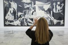 Una mujer fotografía El Guernica, de Pablo Picasso.