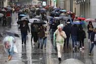 Los viandantes se protegen de la lluvia este sábado en Madrid.