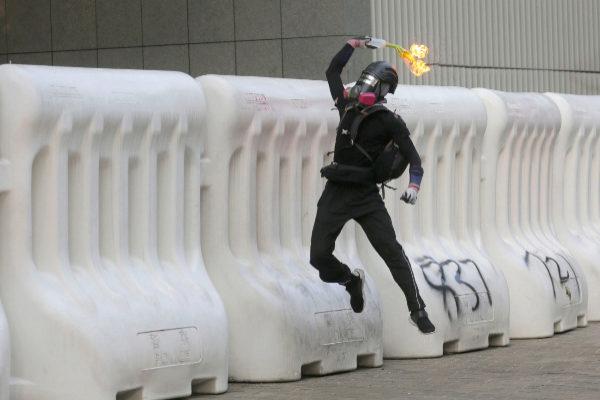 Un manifestante lanza un cóctel molotov durante la marcha de este domingo.