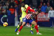 Umtiti (izqda.), junto a Costa en un partido entre el Atlético y el Barça.