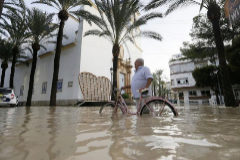 Un hombre pasea ayer sábado con su bicicleta y con el agua por las rodillas en el municipio de Dolores, anegado tras la rotura del cauce del Segura a la altura del puente de Algorfa.