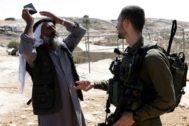 Un palestino discute con un soldado israelí que custodia la demolición de casas palestinas cerca de Hebrón.