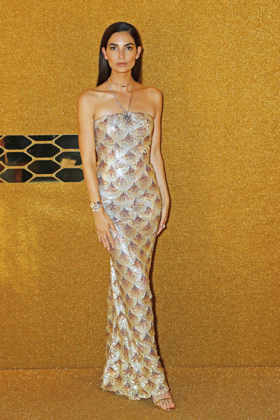 La modelo estadounidense con un vestido sirena estampado en tonos metálicos con escote palabra de honor que combinó con sandalias minimal de tiras doradas.