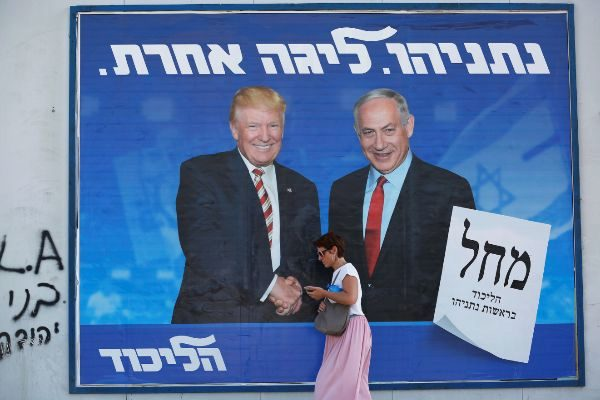 A woman walks past a Likud party election campaign banner depicting...