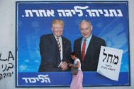 A woman walks past a Likud party election campaign banner depicting Israeli Prime Minister Benjamin Netanyahu and U.S. President Donald Trump in Tel Aviv, <HIT>Israel</HIT>