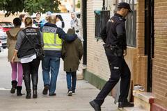 Un policía acompaña al hijo de Fátima, asesinada en Los Pajaritos (Sevilla) el 23 de octubre de 2018