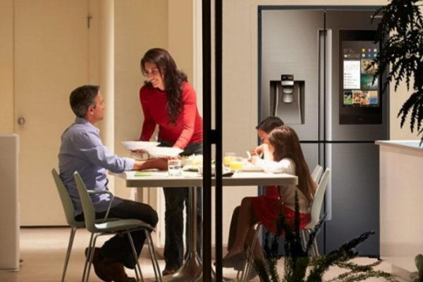 Una familia, en una cocina con un frigorífico de la marca Samsung.