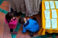 Dos niños cotillean una cabina electoral en Andalucía