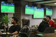 Dos parejas iraníes ven un partido de fútbol en un bar.
