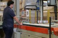 Un trabajador revisa las baldosas de una línea de producción cerámica.