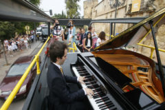 Un músico toca el piano en el bus turístico que recorre Córdoba.