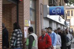 Decenas de personas hacen cola esperando la apertura de una oficina de empleo.