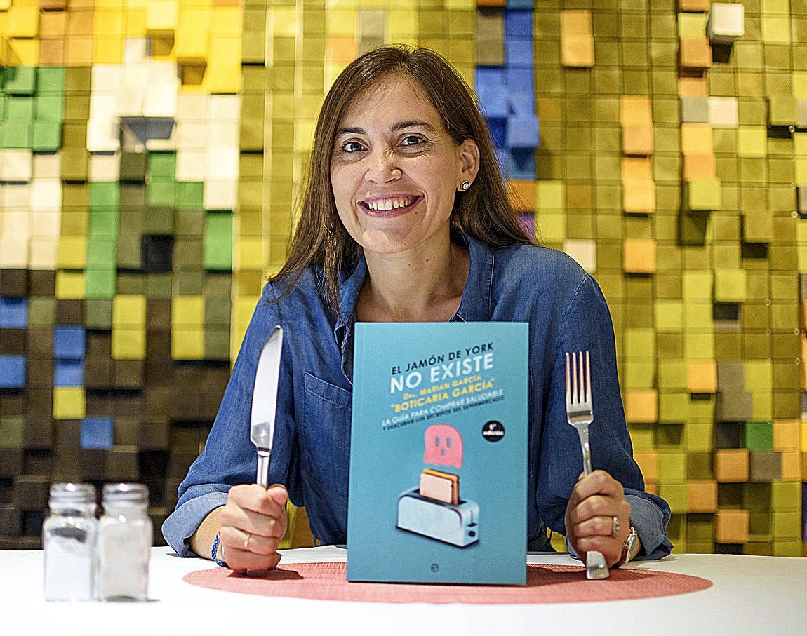 La farmaceútica Marian García posa con su libro sobre la alimentación durante su visita a Bilbao.