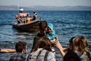 Un grupo de migrantes con un bebeé llegan por mar a las costas de Lesbos.