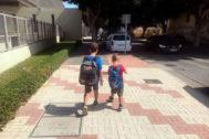 Dos niños van al cole con sus mochilas a la espalda.