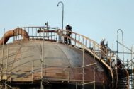 FILE PHOTO: Workers are seen at the damaged site of <HIT>Saudi</HIT> Aramco oil facility in Abqaiq