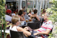 Turistas en una terraza junto a la playa en Alicante.