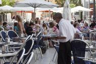 Un camarero en la terraza de un bar en Valencia.