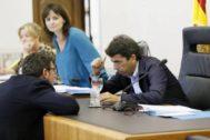 Carlos Mazón (PP) habla con el portavoz de Cs, Javier Gutiérrez, tras acusarle de «deslealtad», bajo la atenta mirada de su compañera Julia Parra.