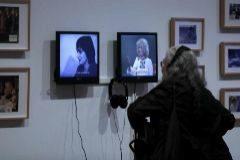 Una mujer observa los vídeos de la exposición 'Musas insumisas'