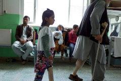 Niños y adultos mutilados de guerra con prótesis caminan por los pasillos de la clínica ortopédica de la Cruz Roja en Kabul.