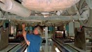 Un técnico inspeccionando los bajos de un automóvil durante la ITV.