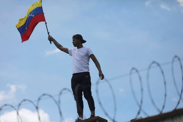 A man holds a Venezuelan flag on the roof of the Consulate of...