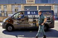 Una furgoneta de Magrudis pasa por delante de la fábrica, durante el registro policial.