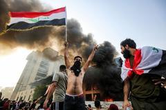Manifestantes frente a un edificio en llamas en Bagdad.