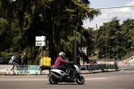 Un repartidor en moto circula por Madrid.
