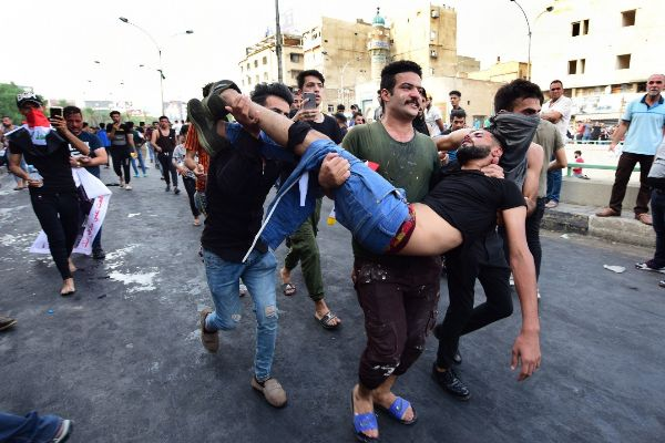 Baghdad (Iraq).- Iraqi protesters carry a wounded man who was injured...