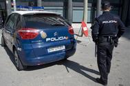Un agente, junto a un coche de la policía.