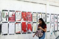 Una mujer camina delante de un muro plagado de carteles de candidatos.