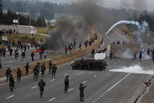 La gente se enfrenta a los soldados mientras bloquean una carretera...