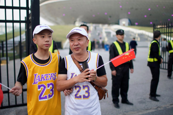 Fans in LeBron James jerseys hold Chinese flags outside the...