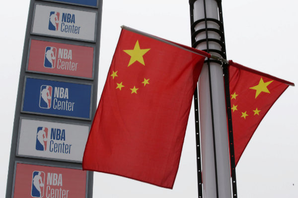 <HIT>NBA</HIT> logos are seen next to Chinese national flags outside a...