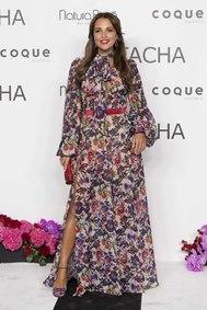 Paula Echevarría eligió un vestido boho de flores largo con una larga abertura hasta la cadera y un sugerente escote cerrado con lazada. Muy sexy, llevó complementos en los mismos tonos, con unas sandalias de tiras en violeta.