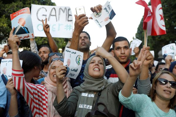 Supporters of Tunisian presidential candidate Kais Saied gesture as...