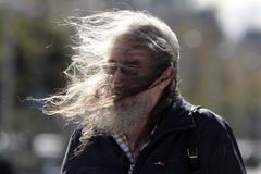 Un hombre paseando por Madrid durante un día con altas rachas de viento.