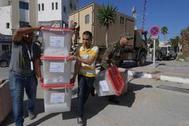 Miembros de la ISIE transportan urnas a un centro de votación, en Ariana.