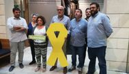 Miquel Ensenyat, en el centro de la imagen, sosteniendo un lazo amarillo.