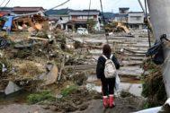 Una mujer frente a casas arrasadas en Nagano, Japón.