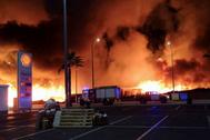 Las llamas calcinan el campamento a poca distancia de una gasolinera.