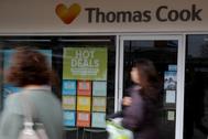 Personas caminan por una tienda cerrada de Thomas Cook en Manchester.