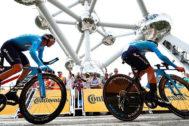 Dos ciclistas de Movistar pedalean en la contrarreloj por equipos durante la salida del Tour de 2019 junto al Atomium de Bruselas.