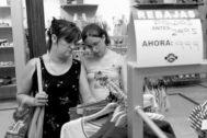 Mujeres mirando los precios en una tienda de ropa usada.