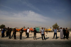 People stand near vehicles in the city of <HIT>Manbij</HIT>